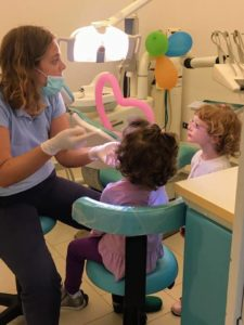ortodontista dentista che fa la prima visita ai bambini