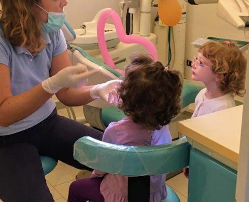 dentista che fa la prima visita ai bambini